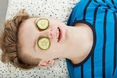 Adolescente que se relaja con las rebanadas del pepino en ojos Fotografía de archivo libre de regalías