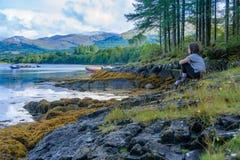 Adolescente que se relaja después de a en el lago Creran, Escocia Imagen de archivo libre de regalías