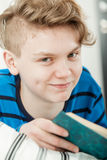 Adolescente que se relaja en cama mientras que libro de lectura Foto de archivo libre de regalías