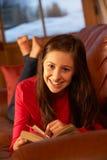Adolescente que se relaja en el libro de lectura del sofá Imagen de archivo