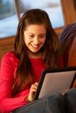 Adolescente que se relaja en el sofá con el ordenador de la tablilla Fotografía de archivo libre de regalías