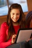 Adolescente que se relaja en el sofá con el ordenador de la tablilla Imágenes de archivo libres de regalías