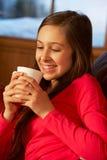 Adolescente que se relaja en el sofá con la bebida caliente Imagen de archivo libre de regalías