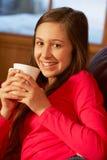 Adolescente que se relaja en el sofá con la bebida caliente Fotos de archivo