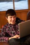 Adolescente que se relaja en el sofá con la computadora portátil Fotografía de archivo libre de regalías