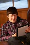 Adolescente que se relaja en el sofá con el ordenador de la tablilla Imagen de archivo libre de regalías
