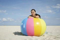 Adolescente que se relaja en la pelota de playa colorida Fotografía de archivo libre de regalías