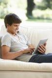 Adolescente que se relaja en la tableta de Sofa At Home Using Digital Fotos de archivo libres de regalías