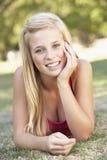 Adolescente que se relaja en parque Imagenes de archivo