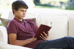 Adolescente que se relaja en Sofa At Home Reading Book Imagenes de archivo