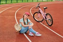 Adolescente que se relaja en un estadio El adolescente se relaja con la bici Foto de archivo libre de regalías