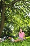 Adolescente que se relaja en un parque con su bicicleta Imagenes de archivo