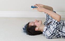 Adolescente que se relaja mientras que en su teléfono celular y que escucha m Foto de archivo