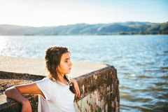 Adolescente que se relaja por el agua Imagenes de archivo