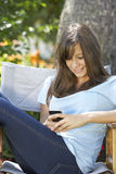Adolescente que se sienta al aire libre en la silla de jardín que manda un SMS en el teléfono móvil Imagen de archivo libre de regalías