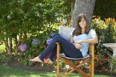 Adolescente que se sienta al aire libre en silla de jardín Foto de archivo