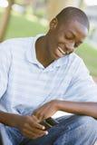 Adolescente que se sienta al aire libre usando el teléfono móvil Imágenes de archivo libres de regalías