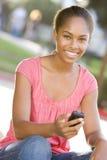 Adolescente que se sienta al aire libre usando el teléfono móvil Foto de archivo