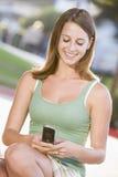 Adolescente que se sienta al aire libre usando el teléfono móvil Imagenes de archivo