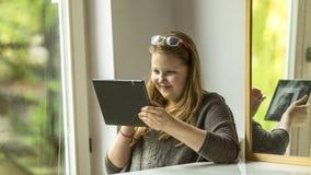 Adolescente que se sienta cerca de la ventana con una tableta a disposición Imagenes de archivo