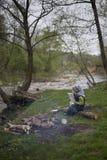 Adolescente que se sienta cerca de un fuego en mapa que acampa y de observación Imágenes de archivo libres de regalías