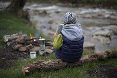 Adolescente que se sienta cerca de un fuego en mapa que acampa y de observación Fotos de archivo libres de regalías