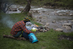 Adolescente que se sienta cerca de un fuego en mapa que acampa y de observación Foto de archivo libre de regalías
