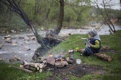 Adolescente que se sienta cerca de un fuego en mapa que acampa y de observación Foto de archivo