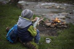 Adolescente que se sienta cerca de un fuego en mapa que acampa y de observación Fotografía de archivo libre de regalías