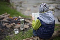 Adolescente que se sienta cerca de un fuego en mapa que acampa y de observación Fotografía de archivo