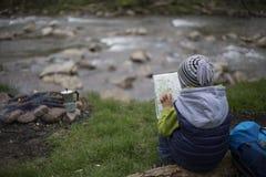 Adolescente que se sienta cerca de un fuego en mapa que acampa y de observación Imagen de archivo