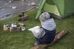 Adolescente que se sienta cerca del fuego y que mira el mapa Foto de archivo