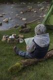Adolescente que se sienta cerca del fuego y que mira el mapa Fotografía de archivo