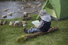 Adolescente que se sienta cerca del fuego y que mira el mapa Fotos de archivo libres de regalías