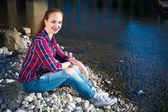 Adolescente que se sienta cerca del lago Imagen de archivo libre de regalías