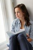 Adolescente que se sienta con el libro por la ventana Foto de archivo