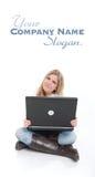 Adolescente que se sienta con el ordenador portátil Foto de archivo