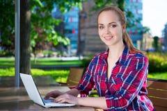 Adolescente que se sienta con el ordenador portátil en café Imágenes de archivo libres de regalías