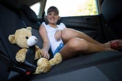 Adolescente que se sienta con el oso de peluche en el asiento trasero del coche Fotos de archivo libres de regalías