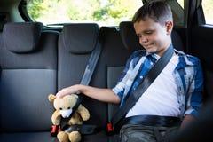 Adolescente que se sienta con el oso de peluche en el asiento trasero del coche Fotos de archivo