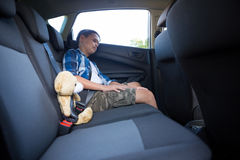 Adolescente que se sienta con el oso de peluche en el coche Foto de archivo