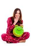 Adolescente que se sienta con el reloj de alarma Foto de archivo libre de regalías