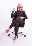Adolescente que se sienta con el sombrero rosado Fotografía de archivo libre de regalías