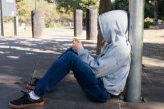 Adolescente que se sienta con el teléfono elegante Imagen de archivo libre de regalías