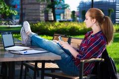 Adolescente que se sienta con el teléfono elegante en café Fotos de archivo