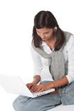 Adolescente que se sienta con la computadora portátil Fotografía de archivo libre de regalías