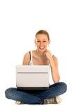 Adolescente que se sienta con la computadora portátil Fotos de archivo libres de regalías
