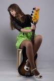 Adolescente que se sienta con la guitarra Fotografía de archivo libre de regalías
