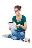 Adolescente que se sienta con la tableta digital Imagen de archivo libre de regalías