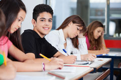 Adolescente que se sienta con los amigos que escriben en el escritorio Foto de archivo libre de regalías
